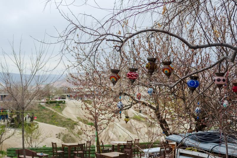Traditional Turkish multicolored lamps on the branches of a tree. Early spring, preparation for the tourist season in Cappadocia.  stock photography