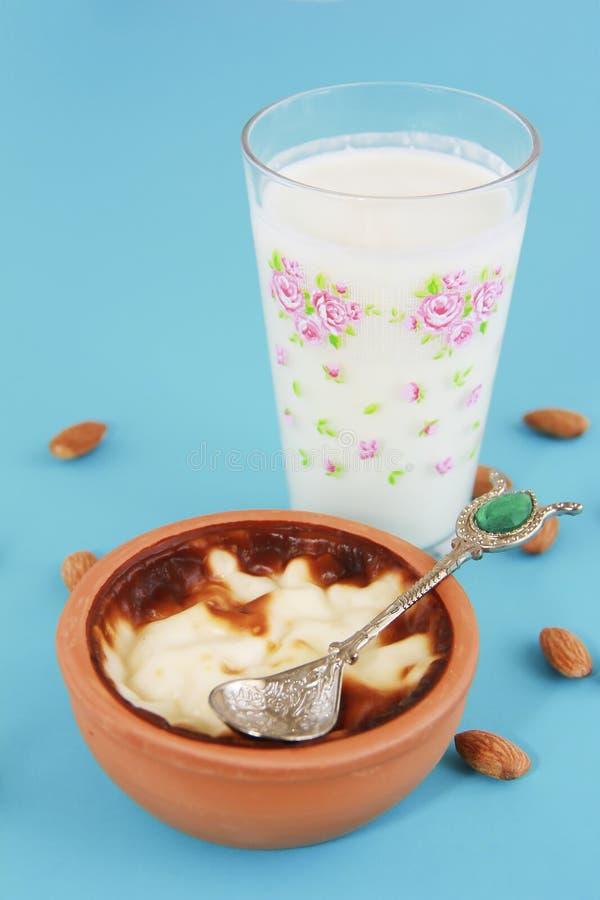 Traditional Turkish sweet supangle dish, a glass of airan and almonds. Traditional Turkish sweet supangle dish, glass of airan and almonds royalty free stock photo