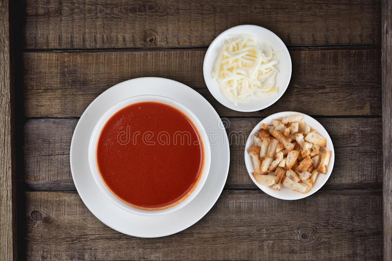 Traditional Turkish tomato soup with cheese and croutons aside on rustic wooden background royalty free stock photography