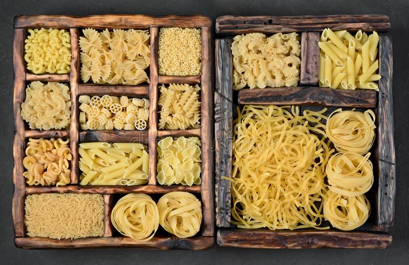 Traditional types and shapes of Italian pasta in vintage wooden boxes. Traditional types and shapes of dry uncooked whole wheat Italian pasta in vintage wooden royalty free stock photo
