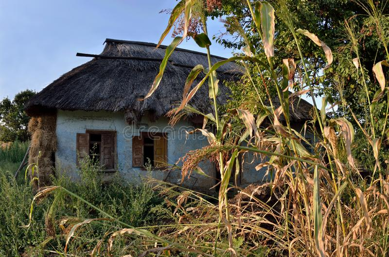 Traditional Ukrainian rural house with rush roof and opened wind royalty free stock photography