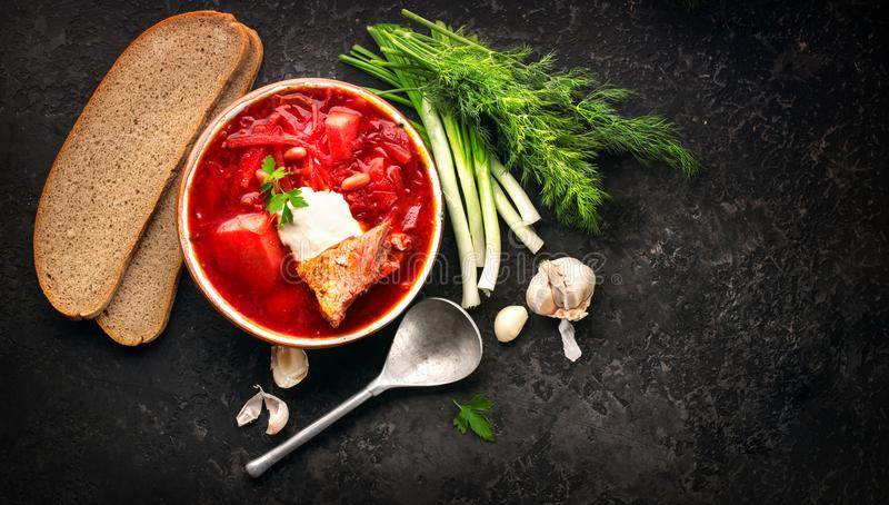 Traditional Ukrainian russian borscht. Plate of red beet root soup borsch on black rustic table. Beetroot soup top view. Traditional Ukrainian cuisine royalty free stock photography