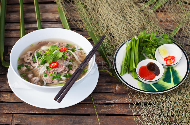 Traditional Vietnamese beef soup pho with sous Hoisin on a wooden background stock photo