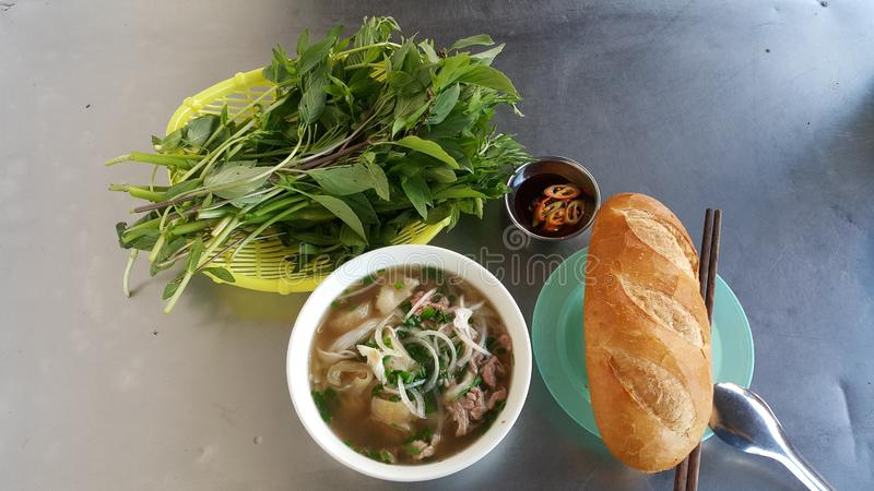 The traditional Vietnamese dishes include Pho with bread and fresh vegetables, chili and soy sauce royalty free stock photo