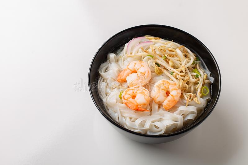 Traditional vietnamese noodle soup pho with shrimps in black bowl. On white background royalty free stock photo