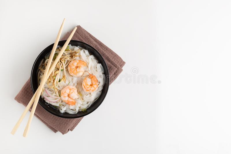 Traditional vietnamese noodle soup pho with shrimps in black bowl. On white background royalty free stock image