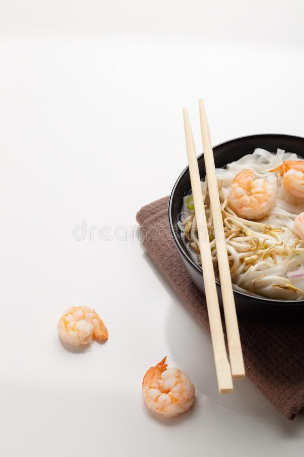 Traditional vietnamese noodle soup pho with shrimps in black bowl. On white background royalty free stock photography