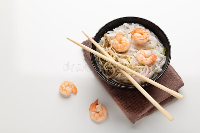 Traditional vietnamese noodle soup pho with shrimps in black bowl. On white background royalty free stock photos