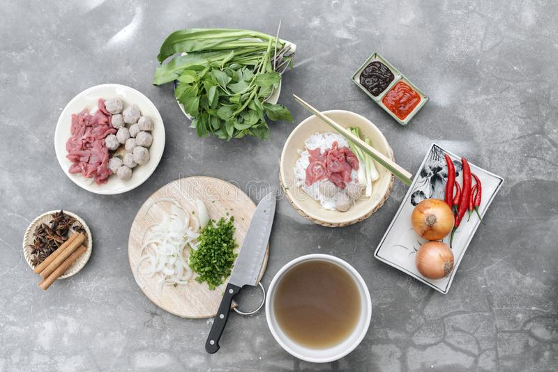 Traditional Vietnamese soup Pho bo with herbs, meat, rice noodles, broth. Pho bo in bowl with chopsticks, spoon. Space for text. T royalty free stock image