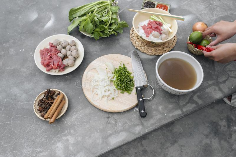 Traditional Vietnamese soup Pho bo with herbs, meat, rice noodles, broth. Pho bo in bowl with chopsticks, spoon. Space for text. T royalty free stock images