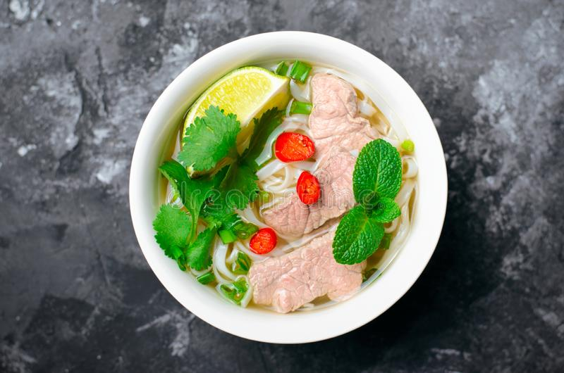 Traditional Vietnamese Soup Pho Bo with Rice Noodles, Beef and Herbs on Dark Background royalty free stock image