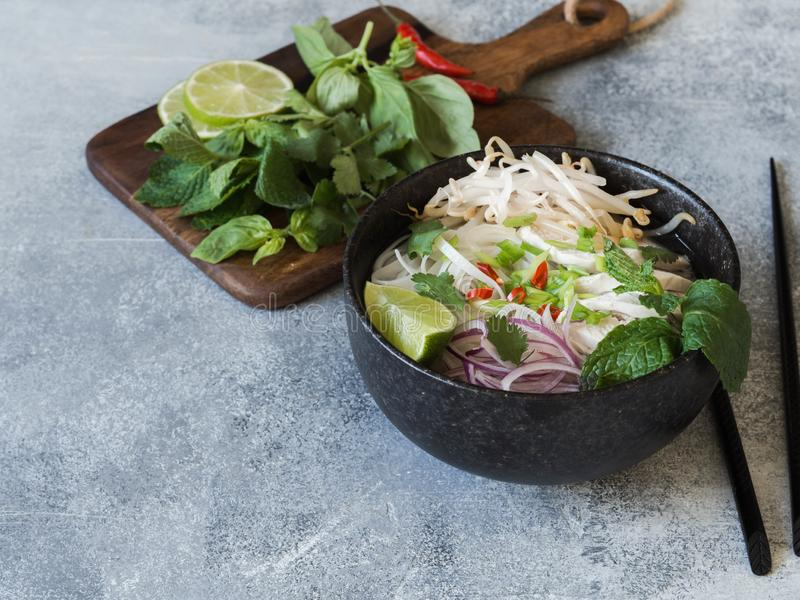Traditional Vietnamese soup- pho ga in black bowl with chicken and rice noodles, mint and cilantro, green and red onion, chili, stock photos