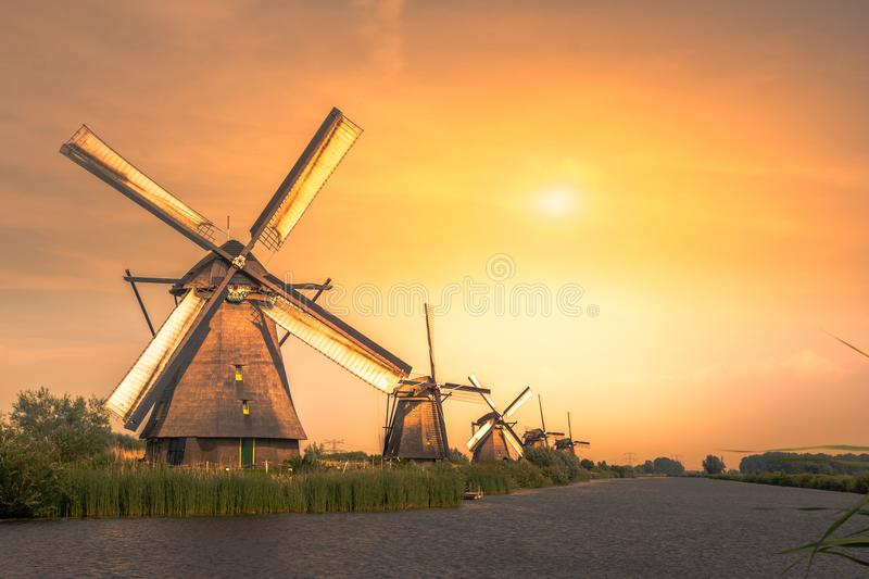 Traditional village with dutch windmills and river at sunset, Holland, Netherlands. Kinderdijk stock photo