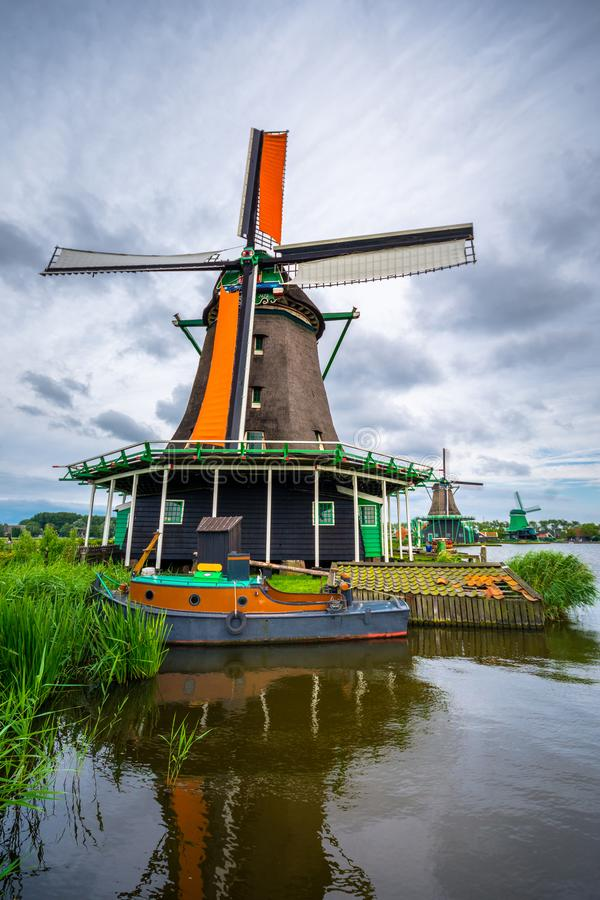 Traditional village with dutch windmills and river at sunset, Holland, Netherlands. stock photo