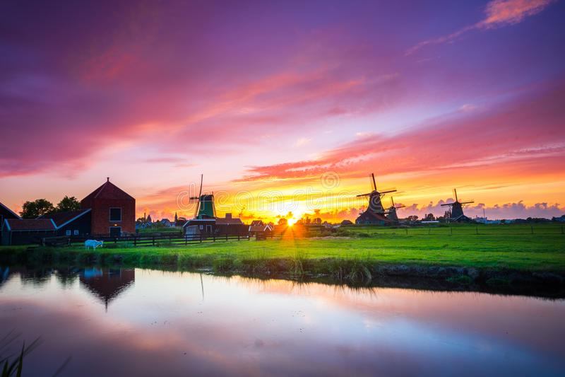 Traditional village with dutch windmills and river at sunset, Holland, Netherlands. Zaanse Schans royalty free stock photography