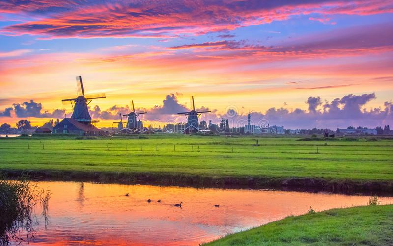 Traditional village with dutch windmills and river at sunset, Holland, Netherlands. Zaanse Schans royalty free stock image