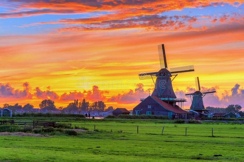 Traditional village at sunset, with dutch windmills, bridge and river on Zaanse Schans, Holland. royalty free stock photo