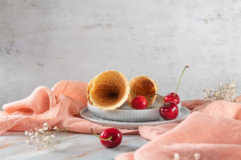 Traditional waffle cones and cherry fruits stock images