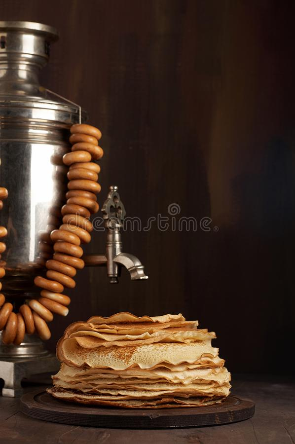 A traditional water boiler pot Russian Samovar with stack of thin pancakes blini royalty free stock images