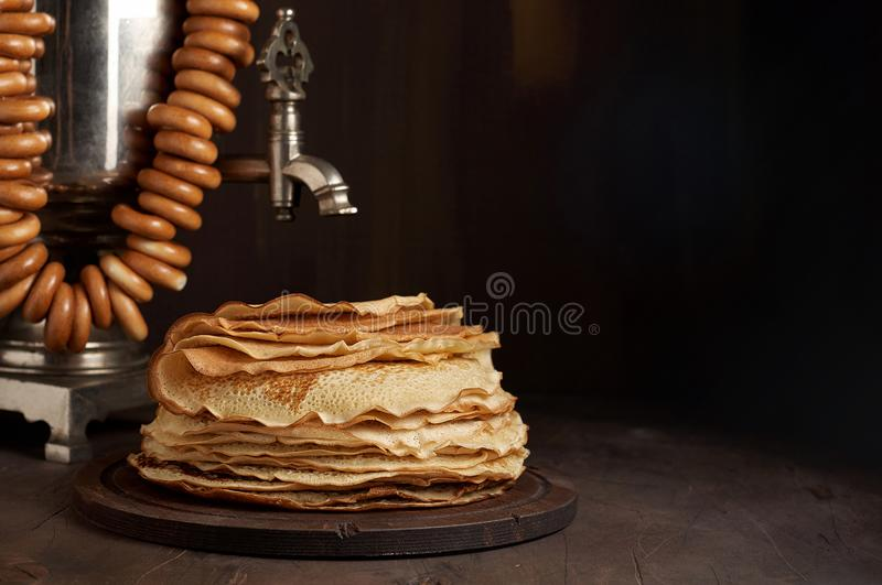A traditional water boiler pot Russian Samovar with stack of thin pancakes blini stock images