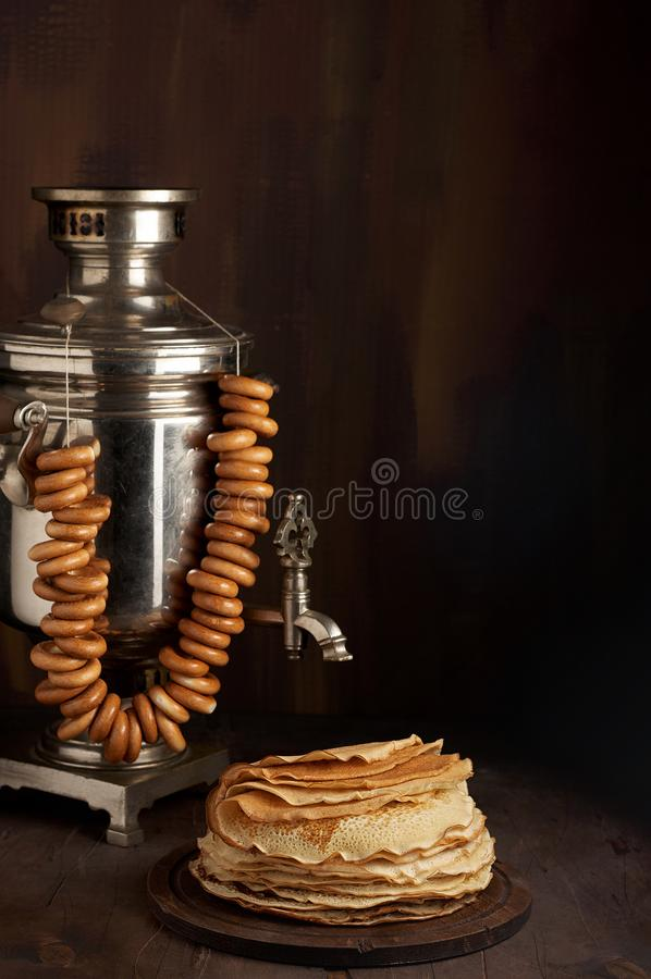 A traditional water boiler pot Russian Samovar with stack of thin pancakes blini stock image