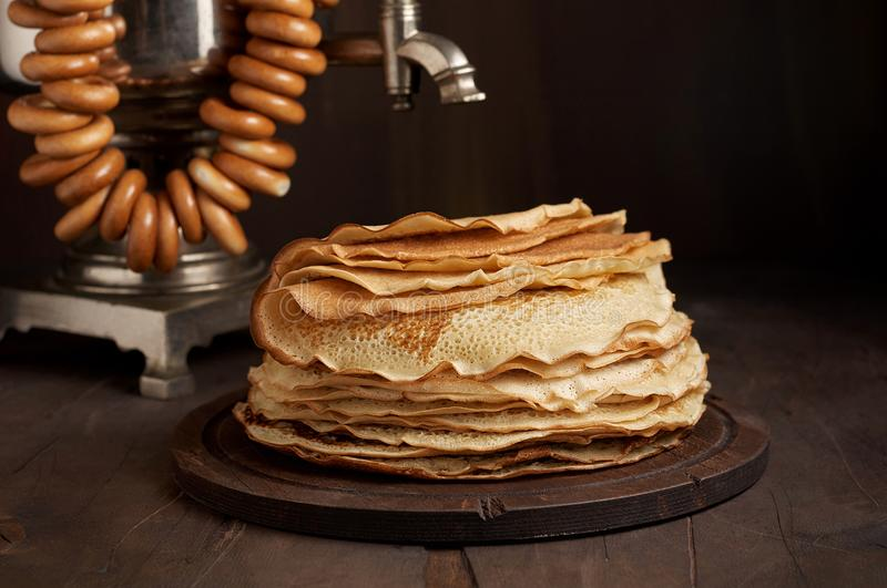 A traditional water boiler pot Russian Samovar with stack of thin pancakes blini royalty free stock image