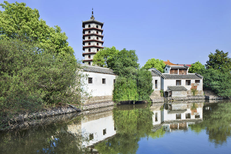 Traditional white Chinese house and pagoda reflected in a canal. stock images