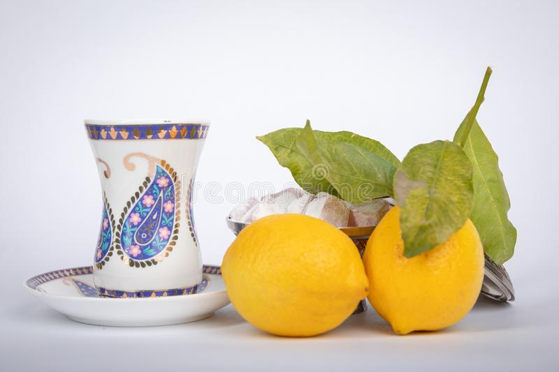 Traditional white color armudu tea Cup with national patterns and buta print. Two lemons with a branch, Turkish delight,in an old copper sugar bowl royalty free stock photography