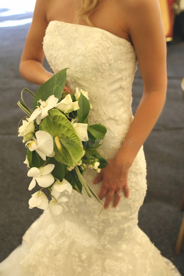Traditional white dress with a bouquet of flowers royalty free stock photo