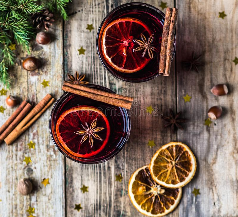 Traditional winter alcoholic drink - mulled wine. Hot wine with fruits and spices in glasses on old wooden background. Top view royalty free stock photo