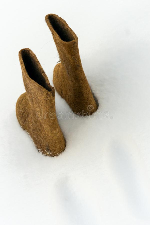Traditional winter shoes felt boots on white snow stock photos