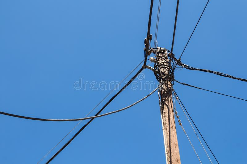 Electricity pole and cables, blue sky. Traditional woden pole for electricity cables. Mountain village Archanes, Crete, Greece royalty free stock photos