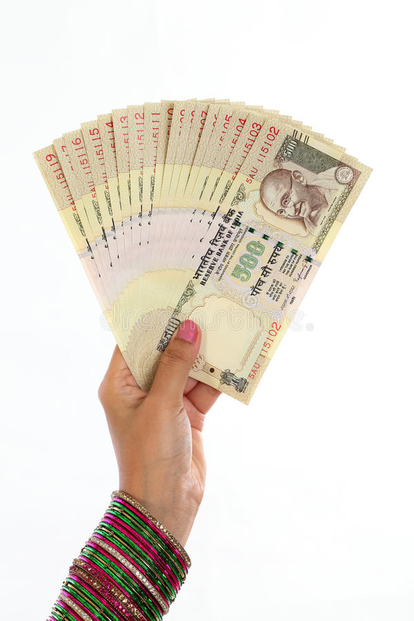 Traditional woman hand holding Indian five hundred rupee notes royalty free stock image