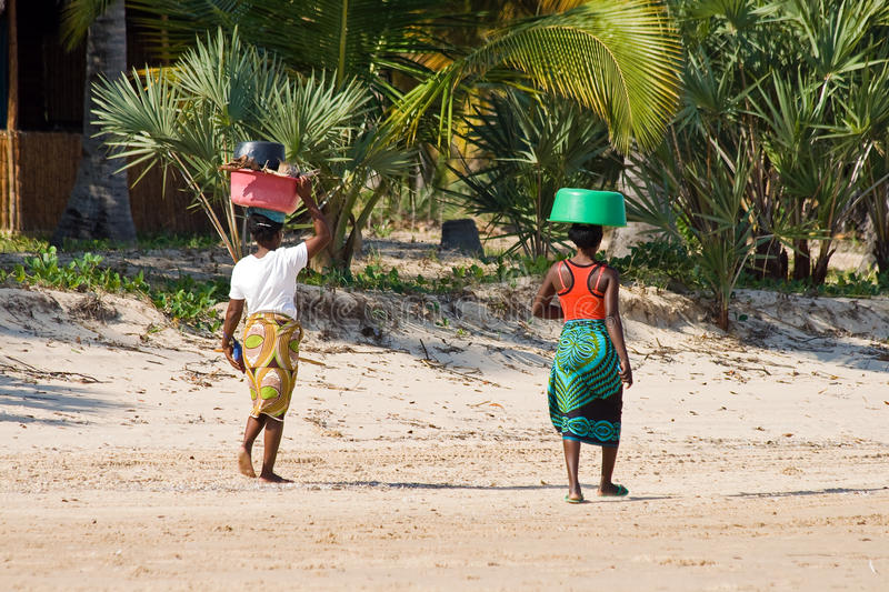 Traditional women walk with bowls on their heads stock image