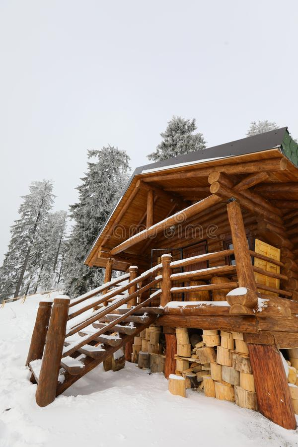 Traditional wood alpine chalet on a mountain slope against forest. In the background photographed from below royalty free stock photography