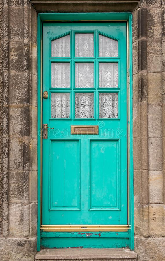 A traditional wooden antique green  door with square glass windows royalty free stock image