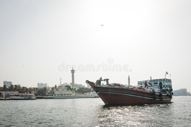 Traditional wooden Arabian boat with goods sailing along the Dubai Creek in Dubai. DUBAI, UAE - February 14, 2018: Traditional wooden Arabian boat with goods stock image