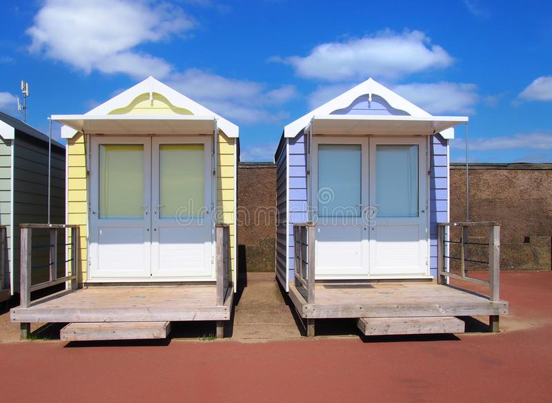 Traditional wooden beach huts painted in bright colours in bright summer sunshine with blue sky and white clouds. Two traditional wooden beach huts painted in stock photo