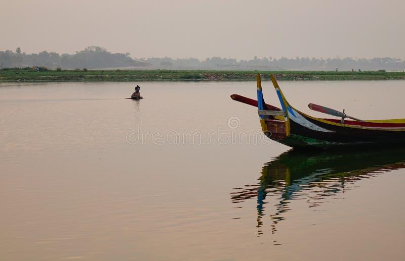 Wooden boats on lake in Mandalay, Myanmar. A traditional wooden boat on lake at sunrise in Mandalay, Myanmar stock photos