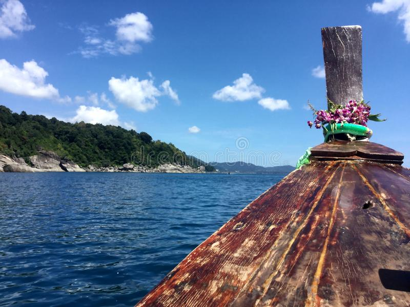 Traditional wooden boat in a picture perfect tropical bay, Thailand, Asia. View of the blue sea with a wooden Thai national boat decorated with live orchids royalty free stock photo