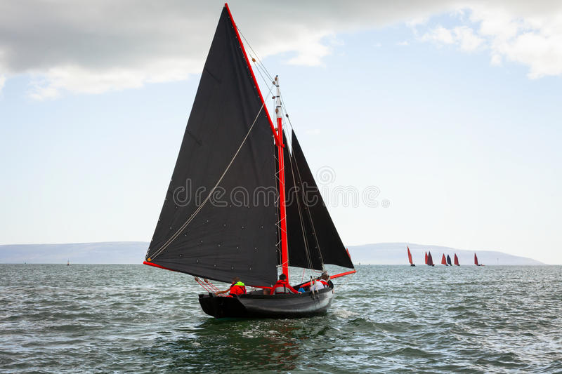 Traditional wooden boats with red sail. stock photo