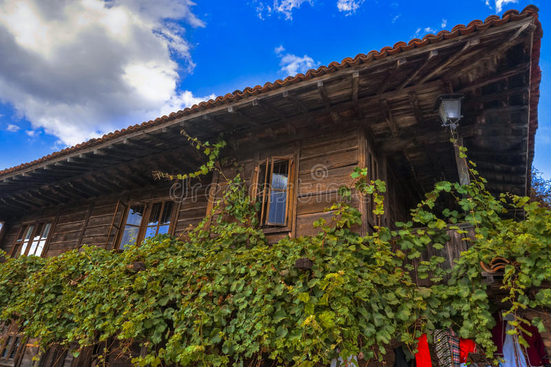 Traditional wooden house with vine in Zheravna Jeravna, Bulgaria, Europe. Traditional wooden house with vine and beautiful sky in Zheravna Jeravna, Bulgaria royalty free stock photography