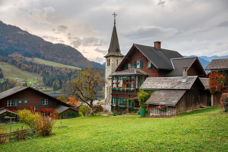 Traditional wooden residential houses on the shore of lake Grundlsee on a cloudy autumn day. Town of Grundlsee, Styria, Austria. Traditional wooden residential royalty free stock photography