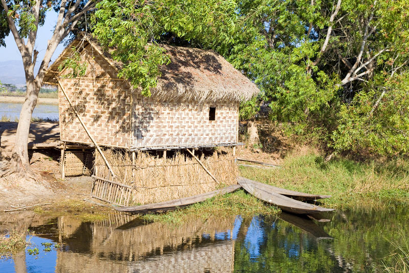 Traditional Wooden Stilt House And Canoe Stock Images