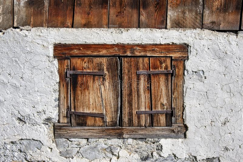 Traditional wooden window shutters of old farm house stock image