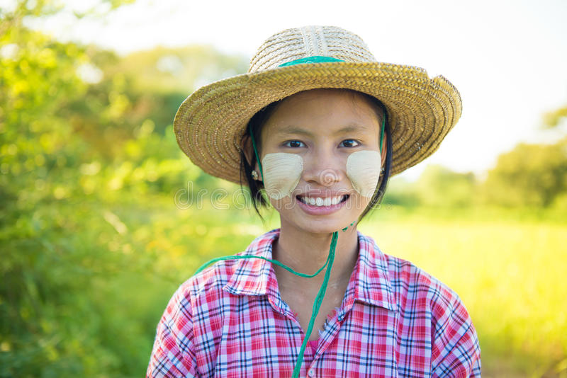Traditional young Burmese female farmer. Portrait of a young Burmese female farmer with thanaka powdered face royalty free stock images