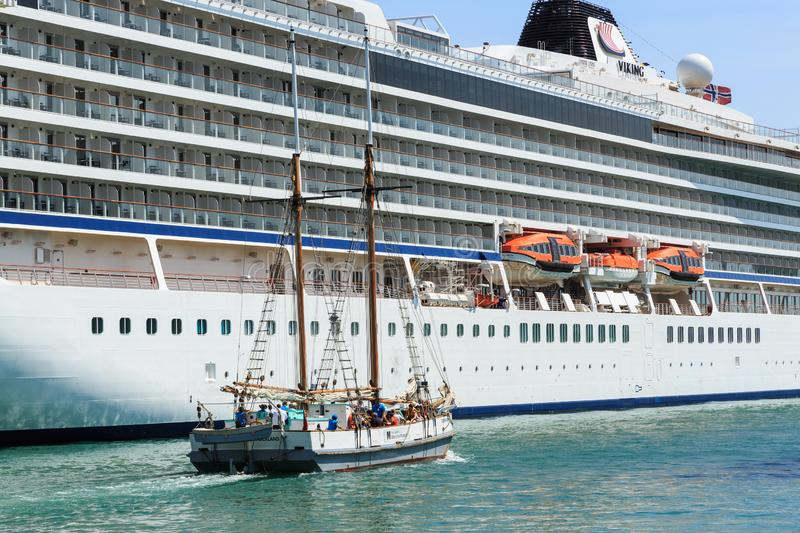 A sailing ship passes a huge cruise liner stock images
