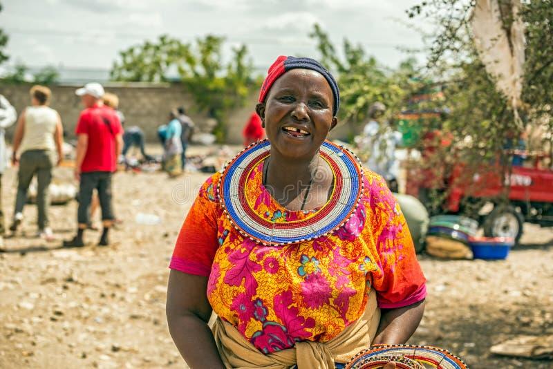 Traditionally dressed african woman from the masai tribe. MTO WA MBU, ARUSHA, TANZANIA - OCTOBER 22, 2014 : Traditionally dressed african woman from the masai stock image