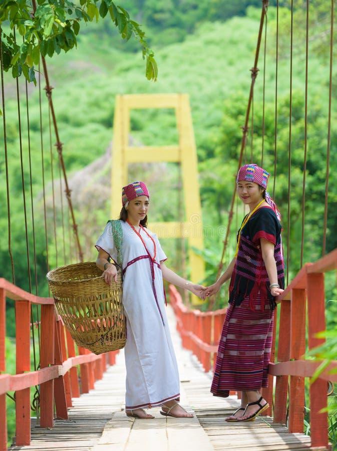 Traditionally dressed Karen hill tribe woman. Traditionally dressed Karen hill tribe women on rope bridge royalty free stock photo