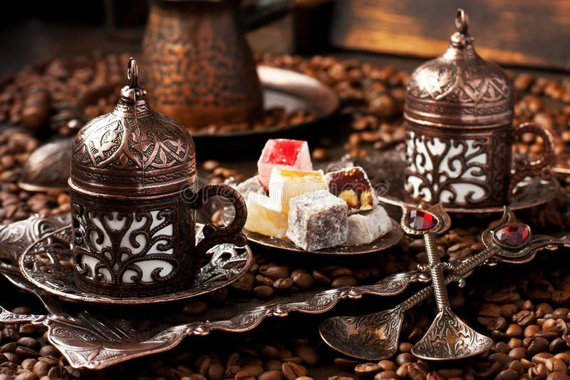 Traditionally served Turkish coffee with eastern sweets. Dark  background  with Turkish coffee cups, aroma beans and eastern sweets royalty free stock images